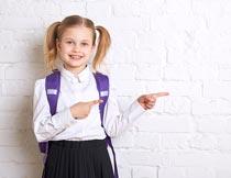 墙壁前作向前手势的女孩摄影图片