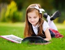 趴在草地上看书的漂亮女孩摄影图片