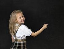 黑板前微笑着拿粉笔的女孩摄影图片