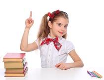 坐课桌前的女孩与书本铅笔摄影图片