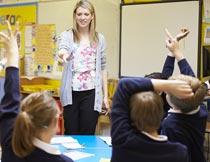 美女老师和积极举手的学生摄影图片