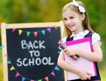 抱着画板和笔回学校的女孩摄影图片