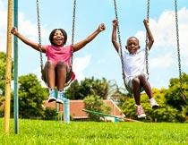 草地上开心荡秋千的儿童摄影图片