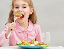 大口吃蔬菜沙拉的漂亮女孩摄影图片