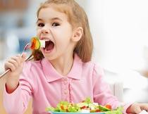 张大嘴巴吃蔬菜的金发女孩摄影图片