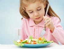 用叉子吃荠菜沙拉的女孩摄影图片