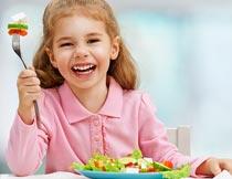 开心的吃蔬菜的漂亮女孩摄影图片
