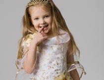 戴桂冠咬手指的可爱小公主摄影图片