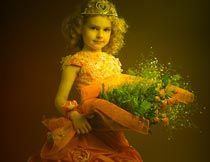 戴桂冠捧花束的美丽小公主摄影图片