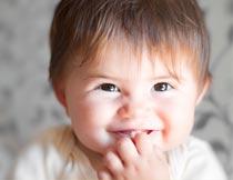 手放嘴上微笑的新生儿局部摄影图片