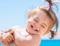 海边眯眼笑的可爱小女孩摄影图片