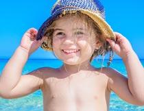 沙滩上双手摸帽子的小女孩摄影图片