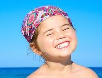 海边眯眼笑的小女孩局部摄影图片