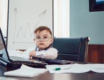 坐在笔记本前办公小男孩摄影图片