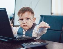 电脑前戴眼镜的帅气小男孩摄影图片