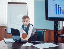 站椅子上电脑办公的小男孩摄影图片