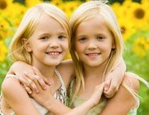 向日葵花海前搂抱的姐妹摄影图片