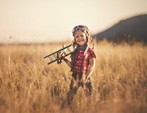 草丛中拿飞机玩具的小男孩摄影图片