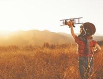 阳光下草地上玩飞机的男孩摄影图片