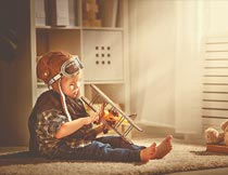 房间坐地毯上玩飞机的男孩摄影图片