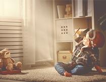 坐在毯子上玩飞机的小男孩摄影图片