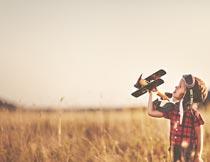 草丛中玩飞机玩具的小男孩摄影图片