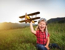 黄昏坐草地上玩飞机的男孩摄影图片