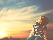 美丽夕阳下戴帽子的小男孩摄影图片