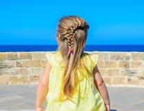 坐着看海的辫子小女孩背影摄影图片