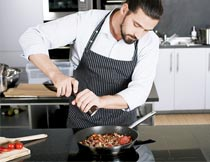 向锅里倒调料的厨师特写摄影图片