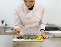 用镊子摆美食拼盘的厨师摄影图片