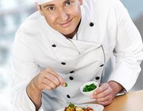 微笑着撒葱花的厨师特写摄影图片