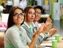坐桌前一群鼓掌的商务男女摄影图片