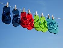 木夹子上的一排彩色的拖鞋摄影图片