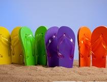 立在沙滩上的彩色人字拖摄影图片