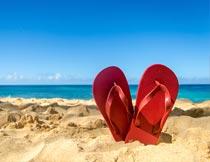 海边立在沙滩上的人字拖鞋摄影图片