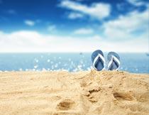 海边立在沙滩上的夏季拖鞋摄影图片