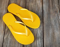 木板上的一双黄色沙滩拖鞋摄影图片