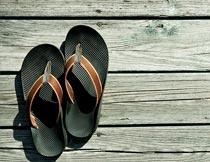 木板上的黑色沙滩拖鞋摄影图片