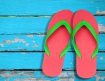 蓝色木板上的红色沙滩拖鞋摄影图片