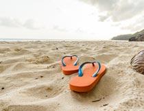 海边沙滩上的橘色人字拖鞋摄影图片