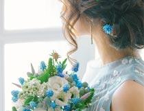站窗前拿花束的美女侧面摄影图片