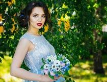 公园里捧着花束的红唇美女摄影图片