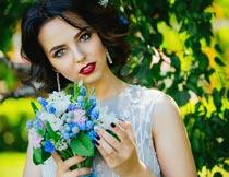 公园里侧脸捧着花束的美女摄影图片