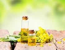 木板上瓶里的菜籽油与花朵摄影图片