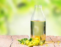 木板上玻璃瓶里的油与花朵摄影图片