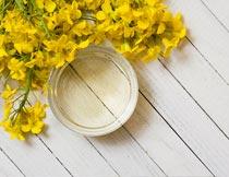 木板上的菜籽油与油菜花摄影图片