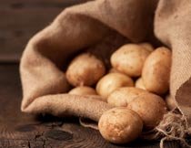 木板上麻袋里的土豆特写摄影图片
