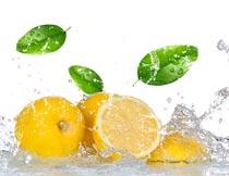 飞溅的水花与新鲜柠檬绿叶摄影图片