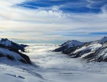 蓝天白云下美丽雪山与云海摄影图片